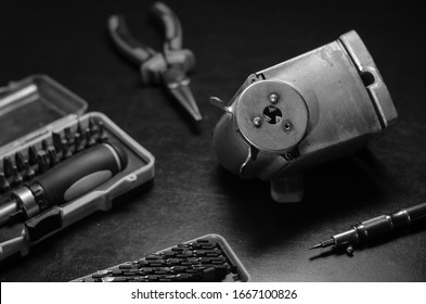 Screw pencil sharpener and tool. Old pencil sharpener and hand tools on a black background. Repair of an old metal pencil sharpener. stationery supplies. Selective focus. Black and white photo.