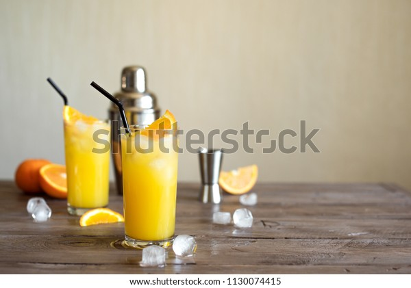 Screwdriver Cocktail with vodka, ice and orange juice. Homemade screwdriver cocktail drink on wooden table, copy space.