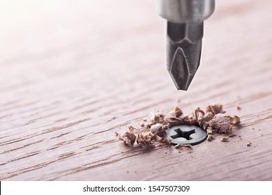 screwdriver screw in a wood oaks plank