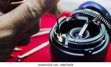 Screwdriver spin repairing into the camera lens body. selective focus.