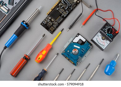 Screwdrivers, a laptop, a solderer, a microscheme and a voltage current resistance analogue multimeter on the grey table, close-up. Assortment of tools.