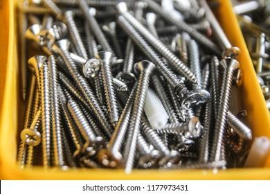 Screws for construction in yellow toolbox, metal screw, iron screw, chrome screw