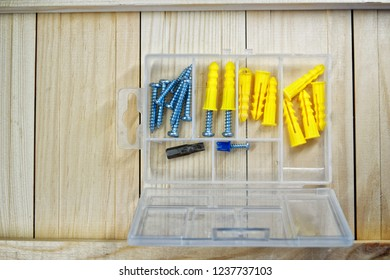 Screws and dowels lie on the boards. Box-organizer for the carpenter. Locksmith work with wood.