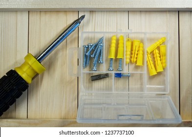 Screws, dowels and screwdriver lie on the boards. Box-organizer for the carpenter. Locksmith work with wood.