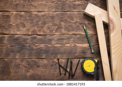 Screws, meter, pencil and wooden bars on the carpenter workbench background flat lay.