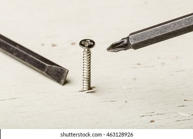 screws on old white wood with screwdriver, choose the right man on the right job concept