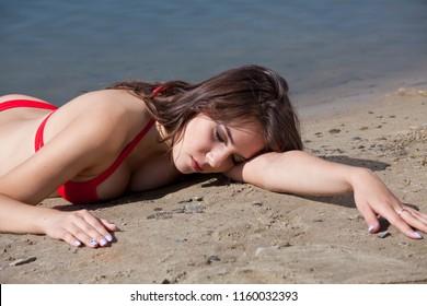 Scripted crime scene on the beach - young woman lying dead in bikini