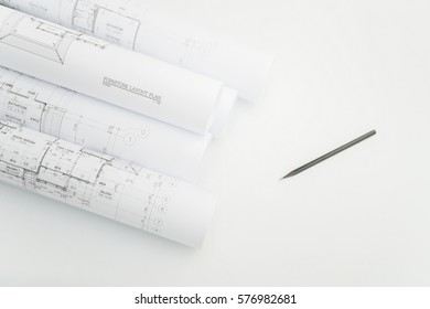 Scroll of architectural drawing and pencil on engineer's working table