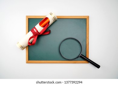 Scroll of certificate, magnifying glass and the black board with copy space , A Flat lay.