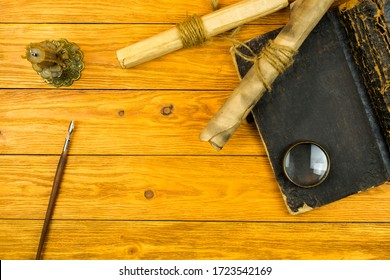 Scroll documents, old big book, pen and candle on a wooden background with space for text. Top view.