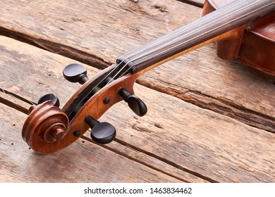 Scroll of the old violin on wooden floor. Construction of vintage cello: scroll and peg box on old wooden planks. Close up design of stringed musical instrument.