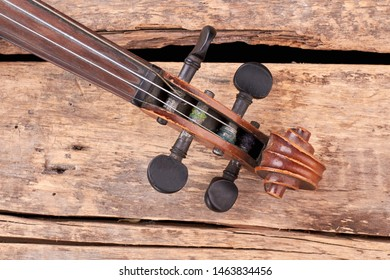 Scroll of the violin on wooden boards. Construction of cello: scroll and peg box. Detail of antique musical instrument.