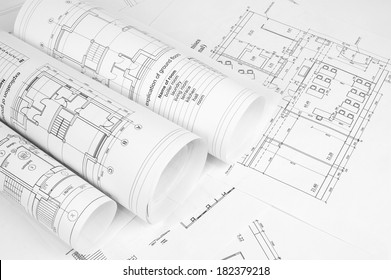 Scrolls of architectural drawings. The desk architect