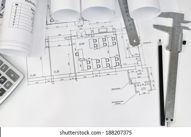 Scrolls of architectural drawings and tools of the architect. The desk architect