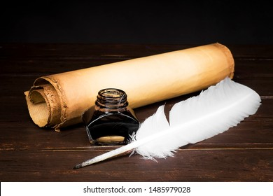 Scrolls of parchment with a stamp, inkwell with a pen on the background of a table top from boards