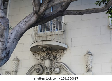 Scrollwork arch under iron balcony framed by tree branch.