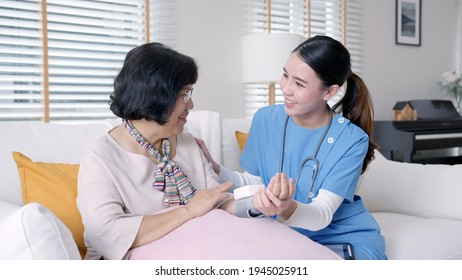 Scrub nurse doctor using digital tonometer check blood pressure for old asia female at home in elderly care cardiovascular medical visit, cholesterol problem and hospice healthcare caregiver concept.