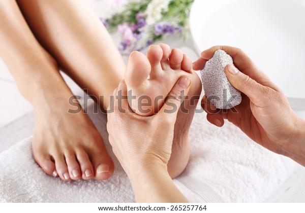 Scrub, schrubben mit Bimsstein tote Epidermis.Fußpflege und Nagel, die Frau am Kosmetiker für Pediküre.
