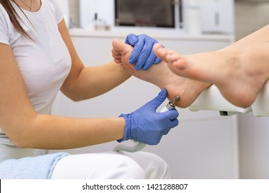 Scrub, scrub with using electric machine dead epidermis. Foot care treatment and nail, the woman at the beautician for pedicure
