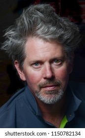 A scruffy, bearded man with wild gray, crazy hair that stands up on end stares intensely forward wearing a blue and green shirt that is shot with strobe lighting in an unusual and unique photograph
