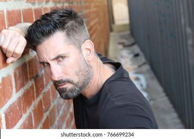 Scruffy handsome urban man leaning on a wall