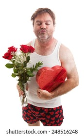 Scruffy middle aged man in his underwear with flowers and candy for Valentines Day, puckering up for a kiss.  Isolated on white.