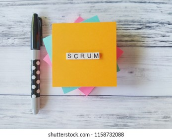 Scrum in letters with  colored notes and black marker on white wood background
