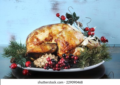Scrumptious roast turkey chicken on platter with festive decorations for Thanksgiving or Christmas lunch, against shabby chic aqua blue rustic wood background.