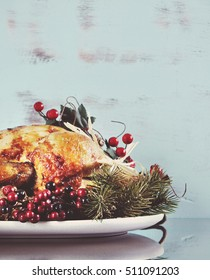 Scrumptious roast turkey chicken on platter for Thanksgiving or Christmas lunch, against shabby chic aqua blue rustic wood background, with applied retro style filters.