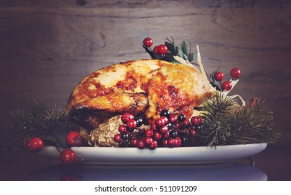 Scrumptious roast turkey chicken on platter for Thanksgiving or Christmas lunch, against dark recycled wood background, with applied retro style filters.