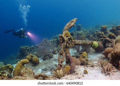 Scuba diver and anchor underwater in tropical sea. Scuba diving reef underwater scenery. Remains of old ship underwater with scuba diver explorer. Adventure scuba diving on the reef with ship wreck.