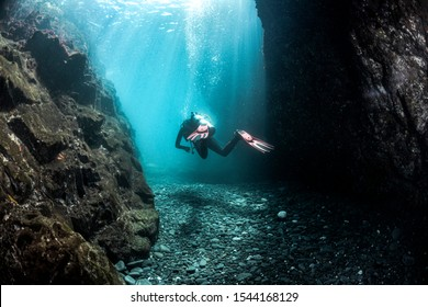 Scuba Diver between walls with beautiful sunlight and shadows