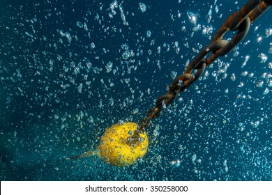 scuba diver bubbles coming from bottom to surface near ship chain