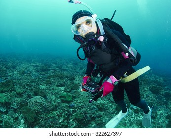 Scuba diver with a camera swims over a colorful tropical coral reef.