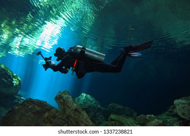 Scuba diver in the cenote, close to the water surface. Scuba diver photographer with underwater camera. Cave diving, limestone rocks. Underwater photography from cenotes exploration.