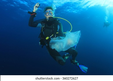 Scuba diver cleans up plastic rubbish pollution discarded in ocean