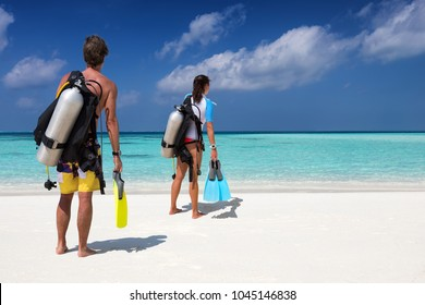 Scuba diver couple with diving equipment on a tropical beach watches the scene