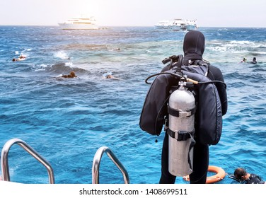 Scuba diver deck of the sailboat, free diving snorkeling in blue ocean on summer vacation. Divers lesson in open water foamy waves.