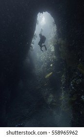 Scuba diver descending into a cave