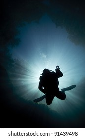 scuba diver descends with the sun behind him