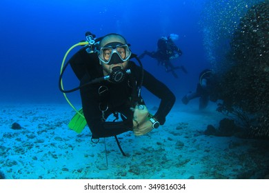 Scuba diver diving explores coral reef in ocean