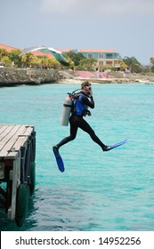 """Scuba diver doing perfect """"giant stride"""" off dock."""
