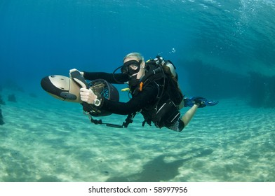 scuba diver drives underwater scooter