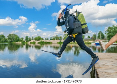 Scuba diver with equipment and flippers jumps in water from pier after boot kick