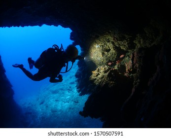 scuba diver exploring the caves caverns and tunnels underwater with his torch light