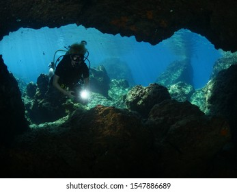 scuba diver exploring caves and fish underwater