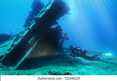 Scuba diver is exploring s sunken wreck in the aegean sea in Greece