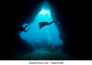 Scuba diver exploring an underwater cave framed in beams of sunlight, Similan, Thailand.