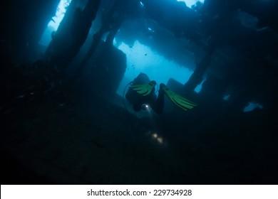 Scuba diver exploring world war II shipwreck in Coron area, Palawan, Philippines.