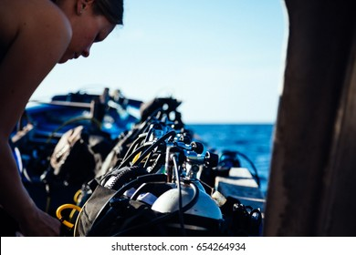 Scuba diver girl female checking dive equipment on the boat on the surface
